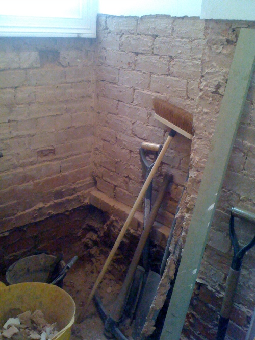 Plaster removed from walls for insertion of chemical damp-proof course.